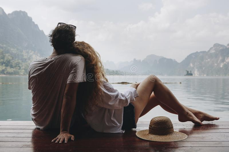 Woman relaxing on her boyfriend at a lake royalty free stock photos