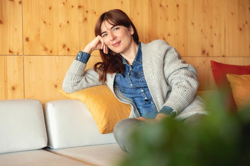 Woman relaxing at home. Beautiful woman sitting and relaxing royalty free stock image