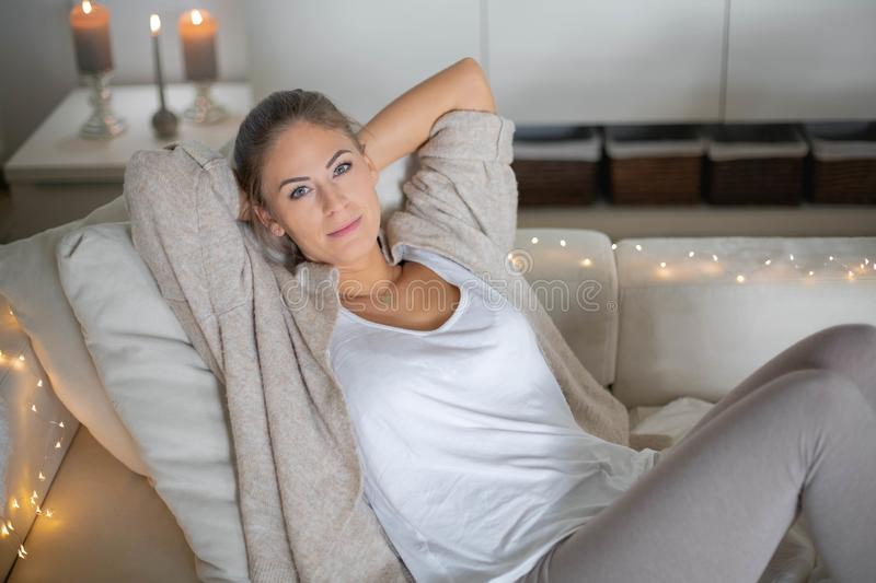 Woman relaxing at home with candles stock images