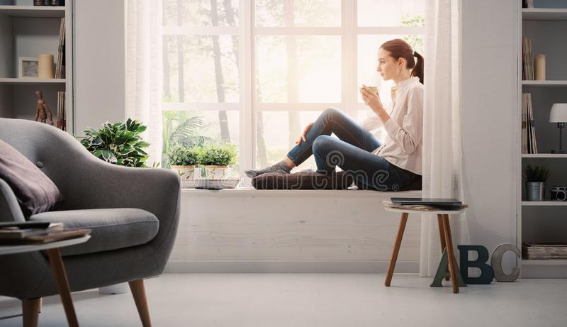 Woman relaxing at home and having coffee stock photo