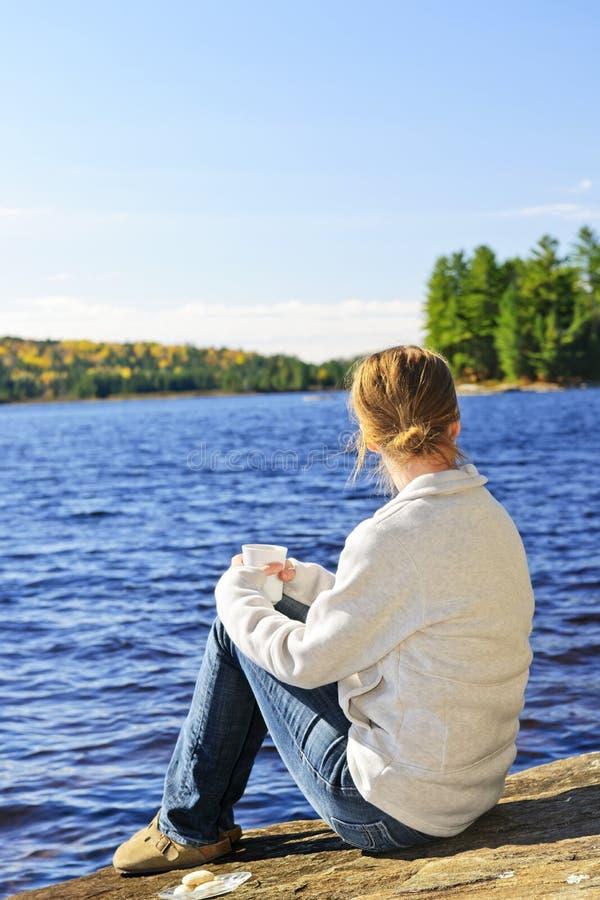 Woman relaxing at lake shore stock photos