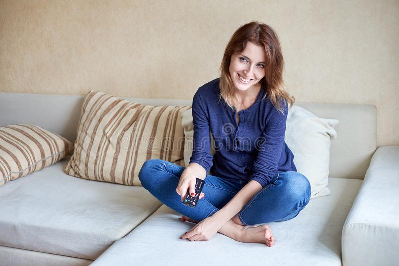 Woman relaxing in living room holding remote control and watching television or tv stock photography