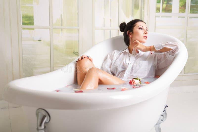 Woman relaxing in milk bath stock image