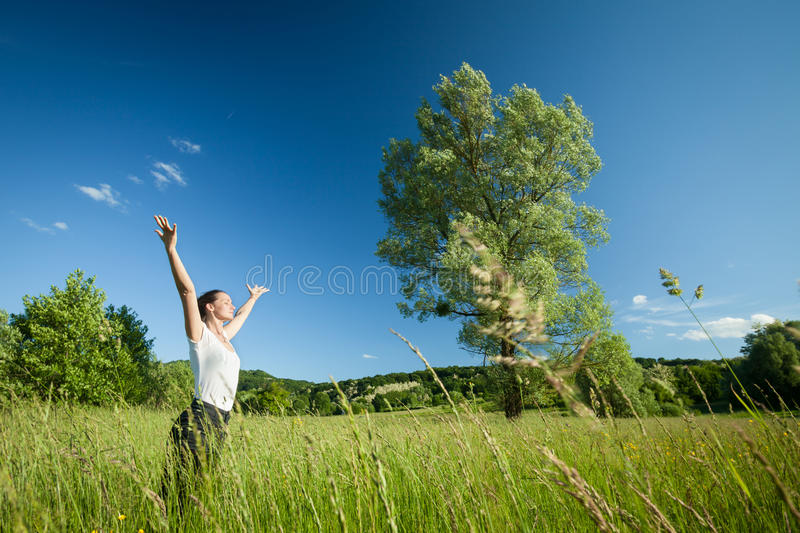 Woman relaxing in nature. Young beautifull woman relaxing with arms raised in nature with tree in background and grass in foreground royalty free stock image