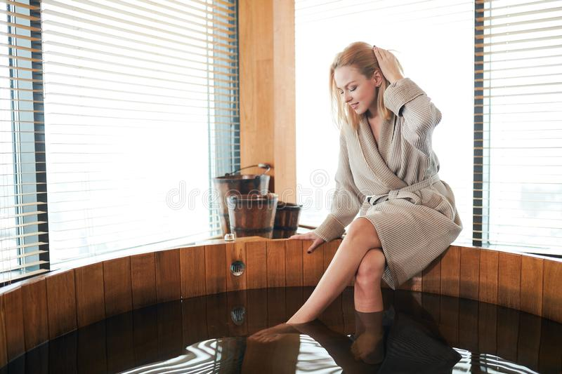 Woman relaxing near wooden barrel bath with glass in spa and sauna concept. Attractive blonde caucasian woman in bathrobe relaxing near wooden barrel bath in spa stock image