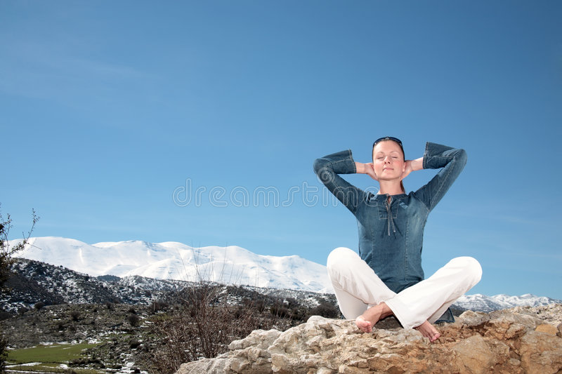 Woman relaxing outdoors. Beautiful young woman relaxing outdoors royalty free stock photography