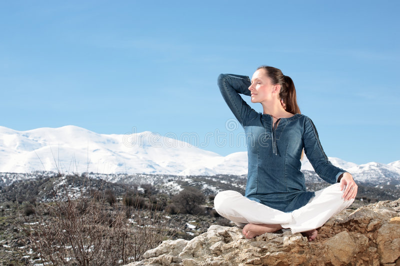 Woman relaxing outdoors. Beautiful young woman relaxing outdoors royalty free stock images