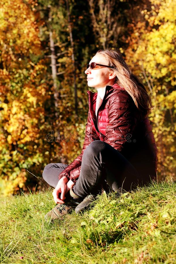 Woman relaxing outdoors autumn nature day outside escaping mental stress Fall foliage royalty free stock image