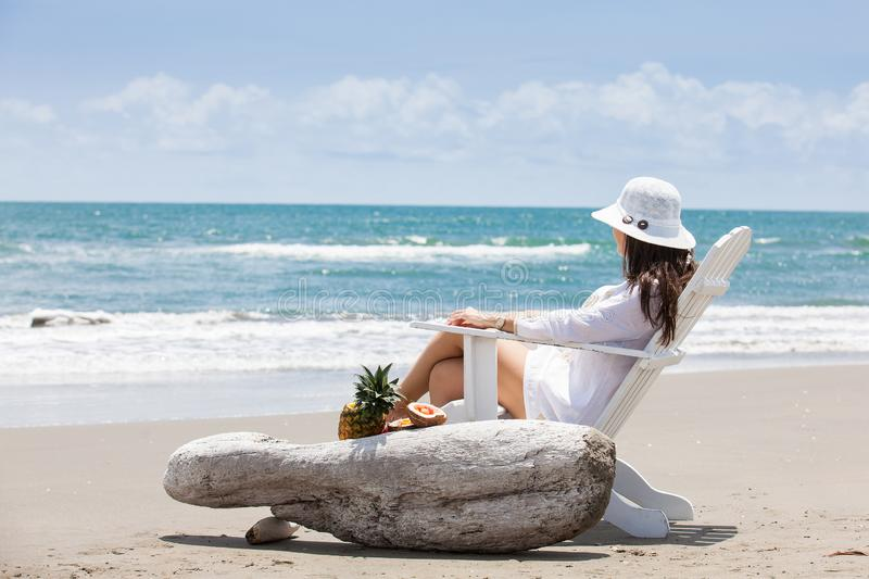 Woman relaxing at a paradisiac tropical beach in a beautiful sunny day royalty free stock photography