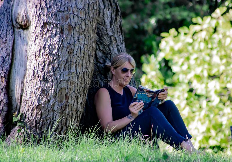 Woman relaxing in a park reading, mature blonde. for many, reading is a way to rest from stress, but it is also very healthy becau. Woman relaxing in a park royalty free stock photos