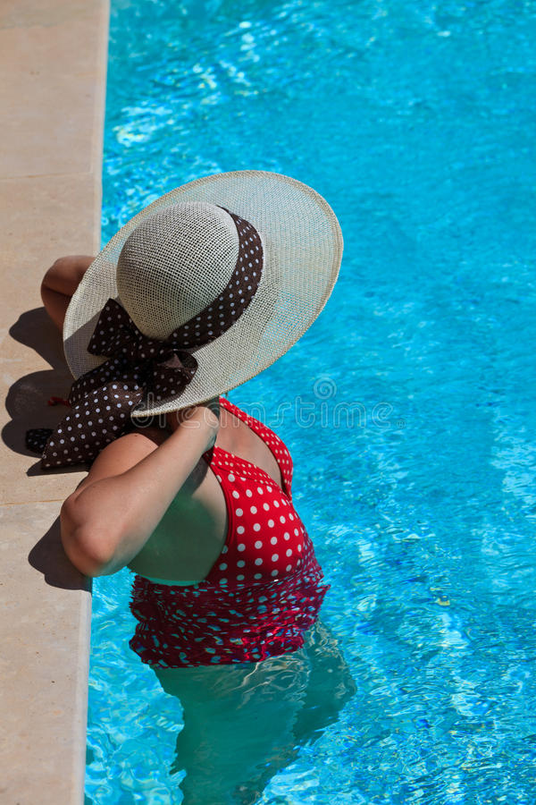 Woman relaxing at the pool stock photography