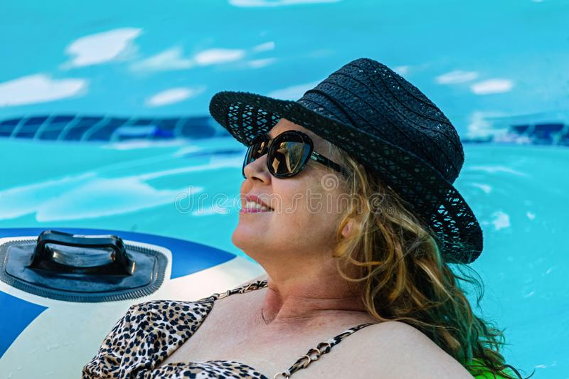 Woman relaxing in the pool stock photos