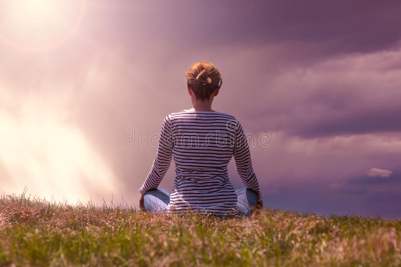 Woman in a relaxing pose on the mountain top royalty free stock images