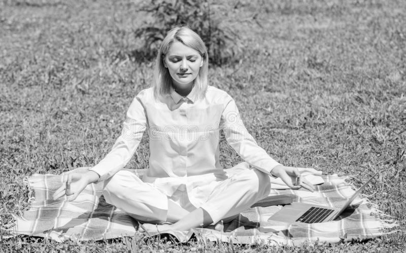 Woman relaxing practicing meditation. Every day meditation. Reasons you should meditate every day. Clear your mind. Girl. Meditate on rug green grass meadow stock photo