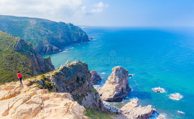 View of Woman relaxing on rocky cliff Cabo da Roca, Portugal stock images