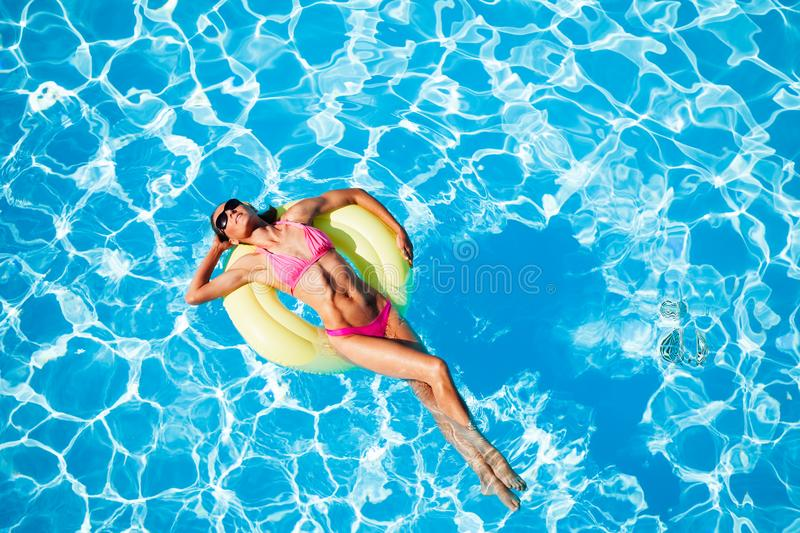 Woman relaxing on rubber ring in the swimming pool royalty free stock photography