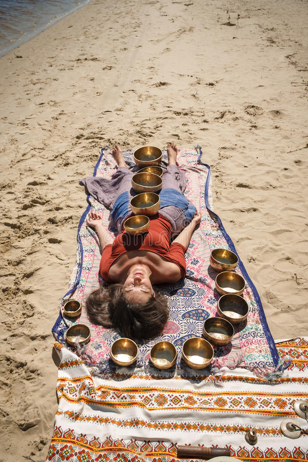 A woman is relaxing with singing bowls on her body royalty free stock photos
