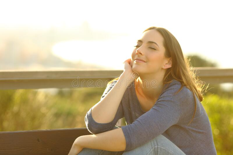 Woman relaxing sitting on a bench at sunset. Satisfied woman relaxing sitting on a bench at sunset outdoors in city outskirts stock images
