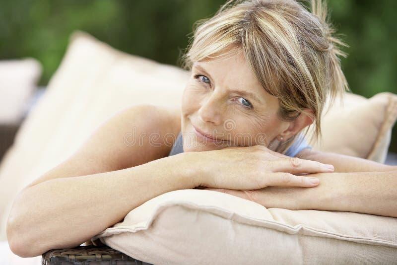 Woman Relaxing On Sofa In Garden stock photo