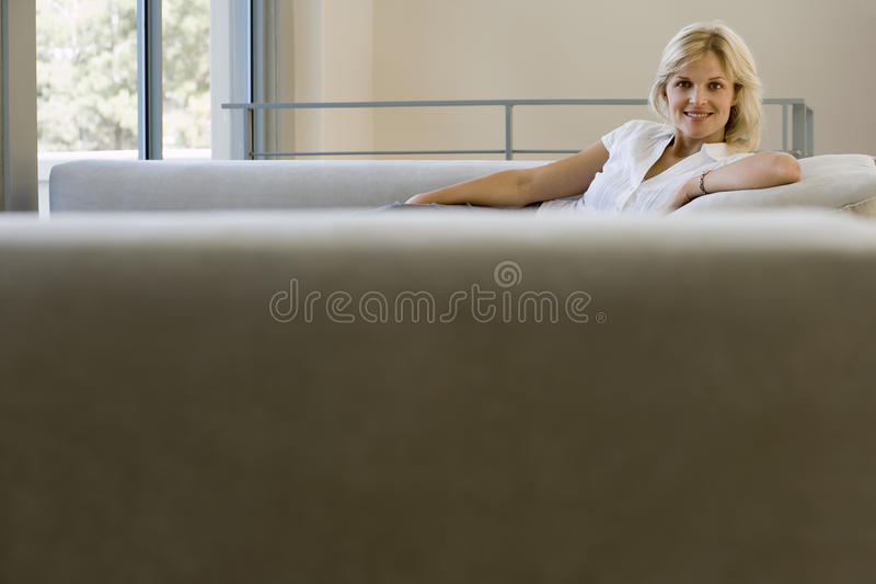 Woman relaxing on sofa at home, smiling, side view, portrait, focus on background stock photo