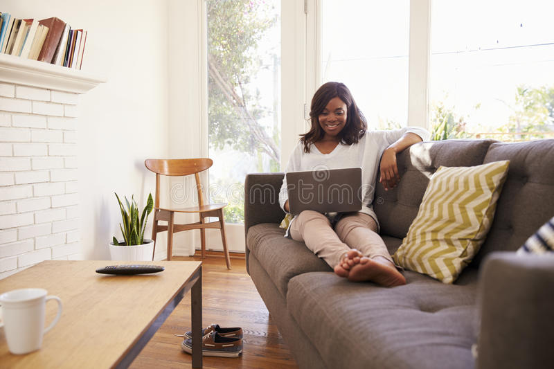 Woman Relaxing On Sofa At Home Using Laptop stock images