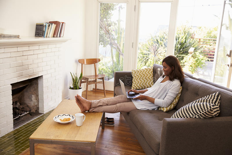 Woman Relaxing On Sofa At Home Using Laptop royalty free stock photos