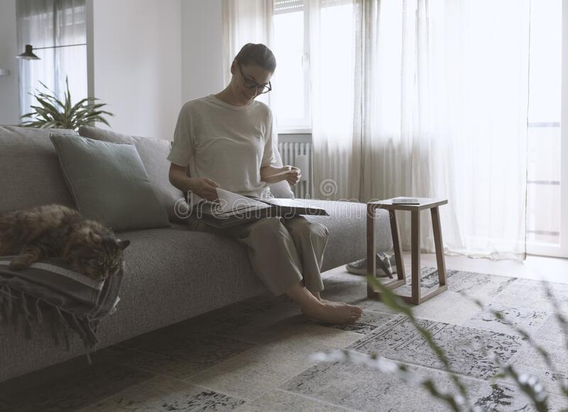 Woman relaxing on the sofa and watching pictures in the photo album royalty free stock images