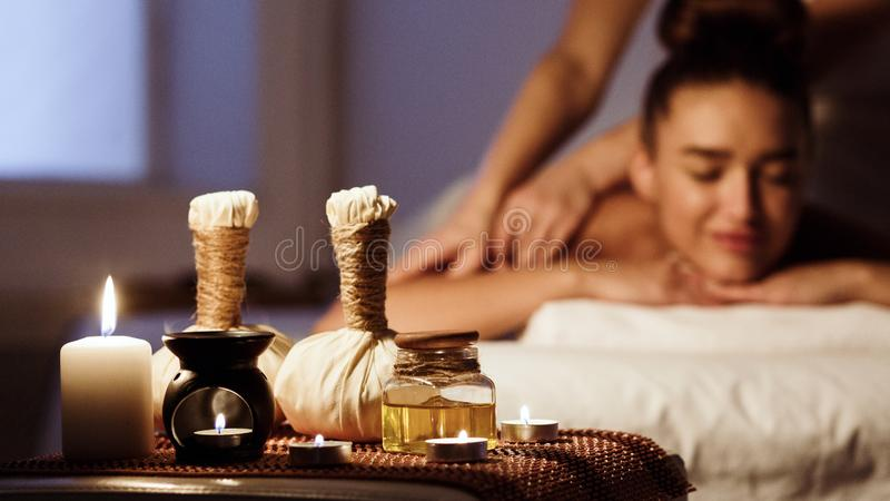 Woman relaxing in spa salon with herbal bags on wooden tray stock photos
