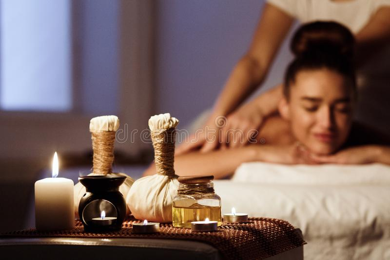 Woman relaxing in spa salon with herbal bags on wooden tray royalty free stock photography