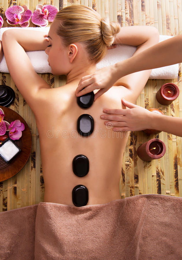 Woman relaxing in spa salon with hot stones on body. royalty free stock photos