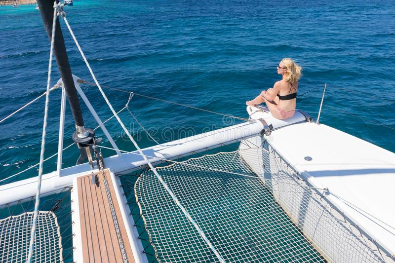 Woman relaxing on a summer sailing cruise, sitting on a luxury catamaran near picture perfect white sandy beach on stock photography
