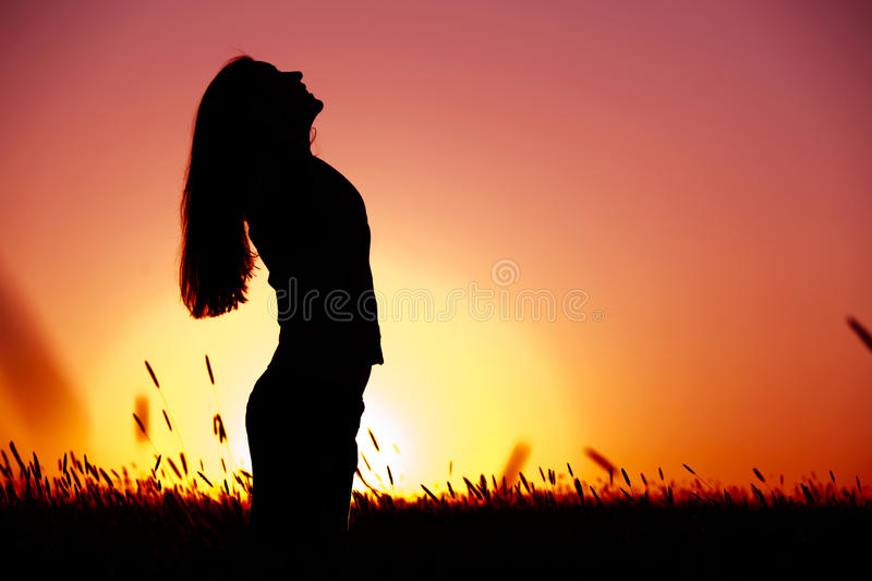 Woman relaxing at sunset stock photo