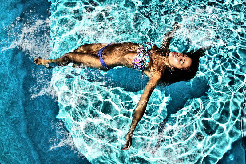 Woman relaxing in a swiming pool stock images
