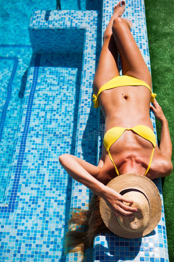 Woman relaxing on the swimming pool water in hot sunny day. Summer holiday idyllic. stock photography