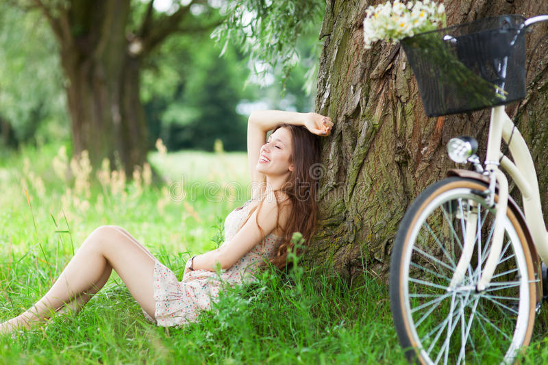 Download Woman Relaxing Under A Tree Next To A Bicycle Stock Photo - Image: 25693480