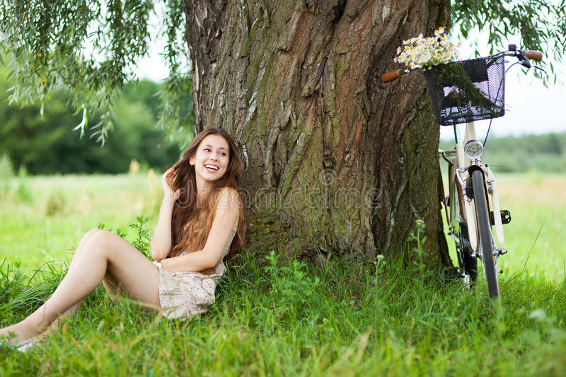 Woman Relaxing Under A Tree Next To A Bicycle Royalty Free Stock Photo