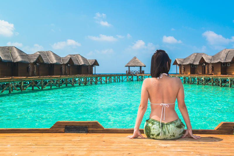 Woman is relaxing on the water bangalow of tropical beach. Woman is relaxing on the water bangalow of the tropical beach, Maldives royalty free stock photography