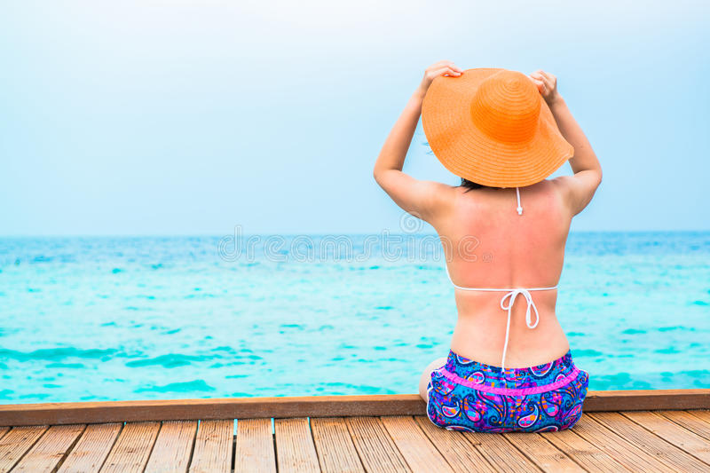 Woman is relaxing on the water bangalow of the tropical beach. Maldives stock photography