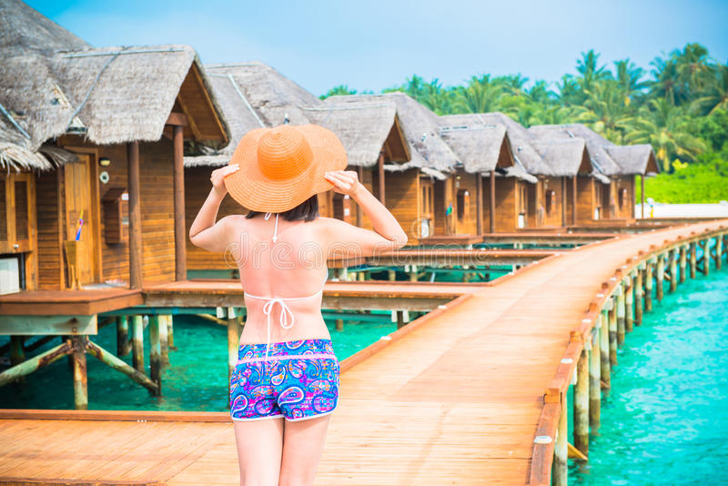 Woman is relaxing on the water bungalow of the tropical beach royalty free stock photos