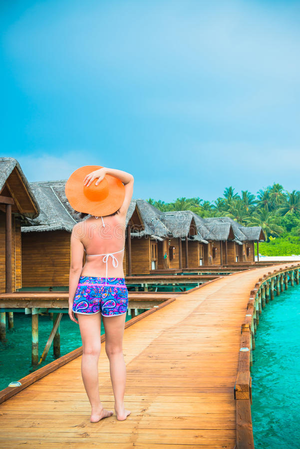 Woman is relaxing on the water bungalow of the tropical beach royalty free stock images