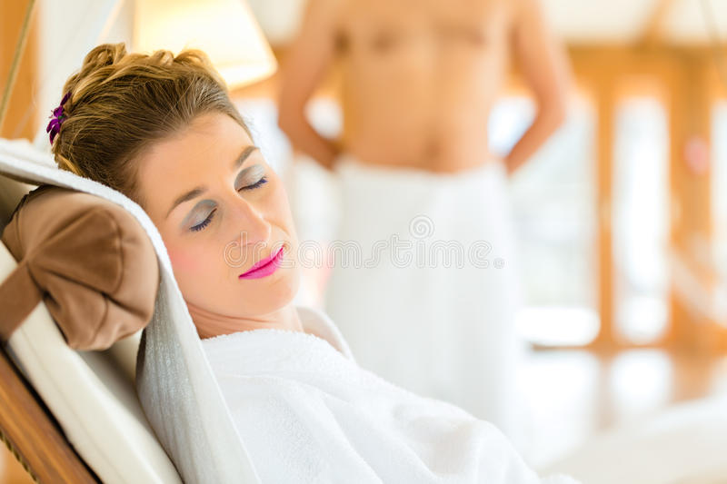 Woman relaxing on wellness spa lounger. Woman in bath robe relaxing or sleeping on swing lounger in wellness spa relaxation room royalty free stock photography