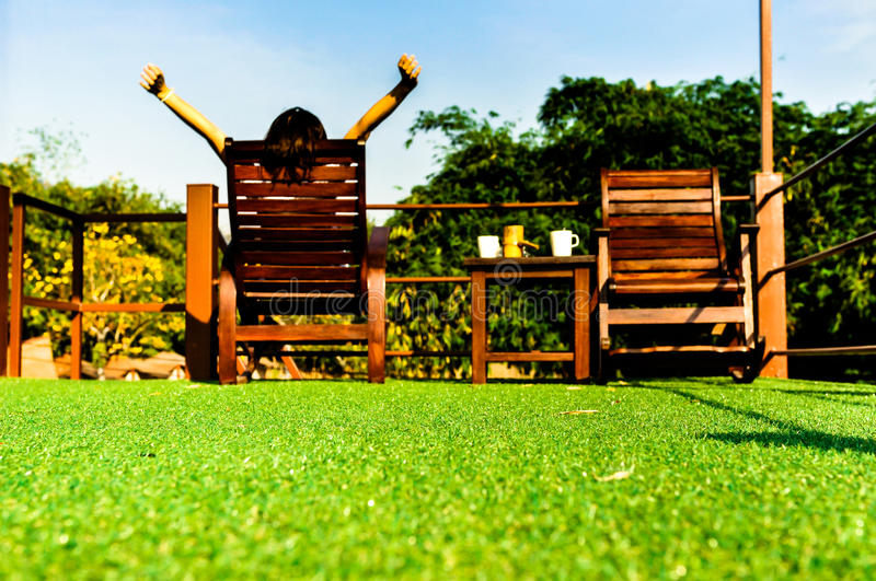 Woman relaxing on wooden sunbed on green artificial grass and looking the blue sky royalty free stock photo
