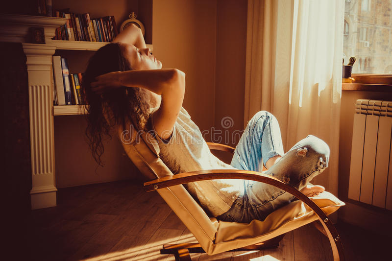 Woman relaxing after work in comfortable modern chair near window in livingroom. Warm natural light. Cozy home. Casual clothing. C stock photos