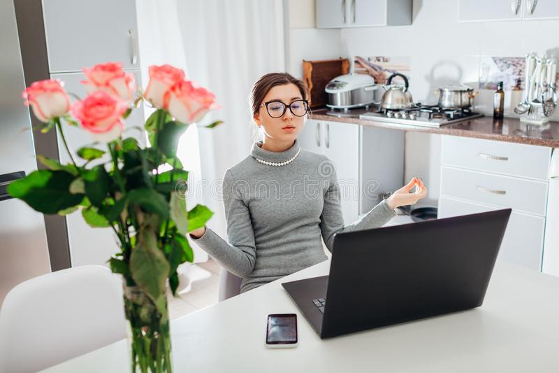 Woman relaxing after working on laptop on modern kitchen. Young tired freelancer meditating. To calm down stock photo