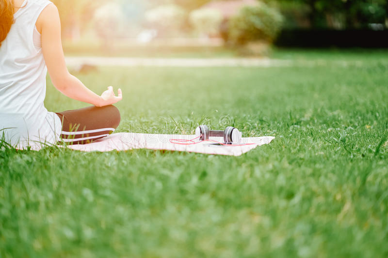Woman relaxing Yoga in the park, Meditation for peace of mind. stock image