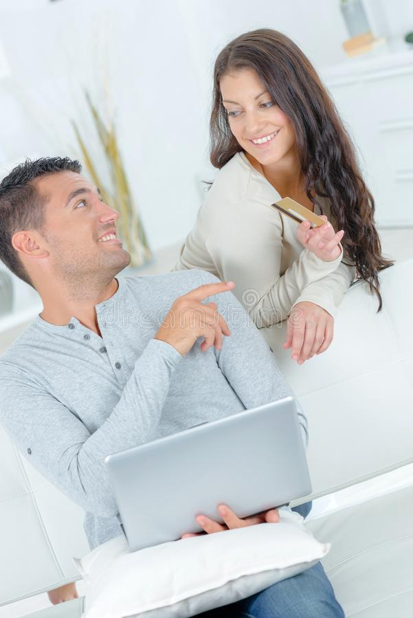 Woman reluctant to give credit card to boyfriend. Accomplice stock images
