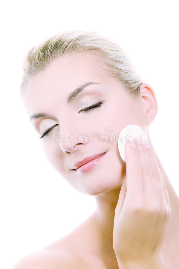 Woman removing cosmetics. Beautiful young woman removing cosmetics with cleansing pad. Toned in blue stock photos