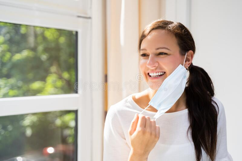 Woman Removing Face Mask. To Breath Freely stock images
