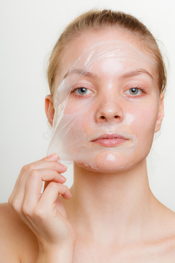 Woman removing facial peel off mask. Beauty skin care cosmetics and health concept. Young woman face, girl removing facial peel off mask. Peeling stock photo