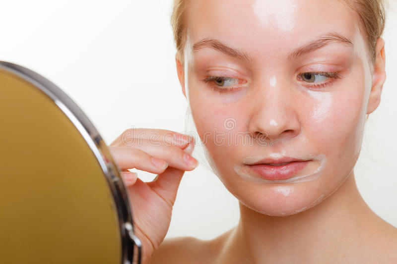Woman removing facial peel off mask. Beauty skin care cosmetics and health concept. Young woman face, girl removing facial peel off mask. Peeling royalty free stock images